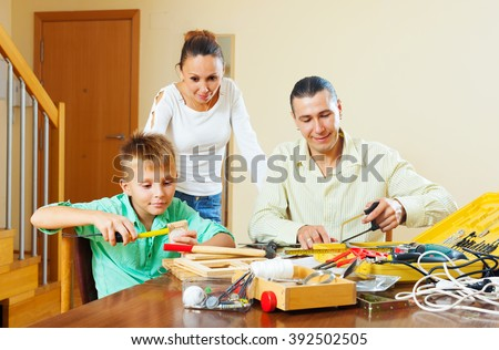 Father and boy spend their free time with working tools at home,  woman watching them   - stock photo