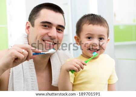 father and child boy brushing teeth before going to bed - stock photo