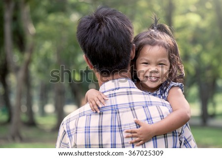 Father and child,happy little girl resting on her father's shoulder in the park, vintage filter effect - stock photo