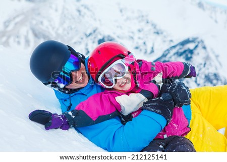 Father and child in ski equipment playing in snow - stock photo