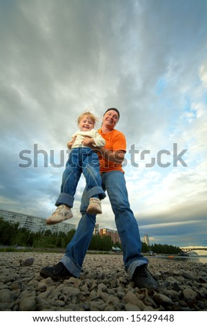 father and child outdoor on stones and river - stock photo