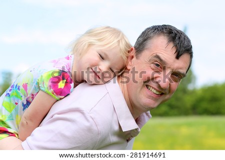 Father and child playing outdoors. Happy active man enjoying time together with his cute little daughter in the park on sunny summer day. - stock photo