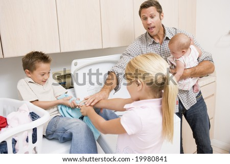 Father And Children Doing Laundry - stock photo