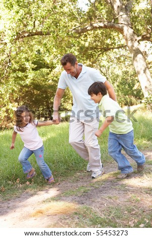 Father And Children Enjoying Walk In Park - stock photo