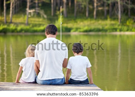 Father and children fishing in the lake - stock photo