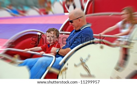 Father and children having fun on spinning amusement park ride - stock photo