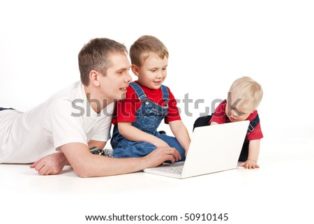 Father and children lying on the floor with laptop - stock photo