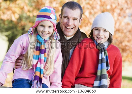 Father and children on autumn walk sitting on fence