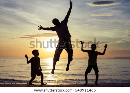Father and children playing on the beach at the sunset time.  People having fun on the beach. Concept of friendly family and of summer vacation.
