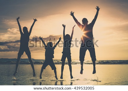 Father and children playing on the beach at the sunset time. People having fun on the sea. Concept of friendly family and of summer vacation. - stock photo
