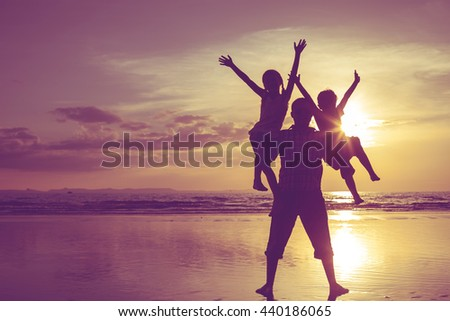 Father and children playing on the beach at the sunset time. People having fun on the sea. Concept of friendship forever and of summer vacation. - stock photo