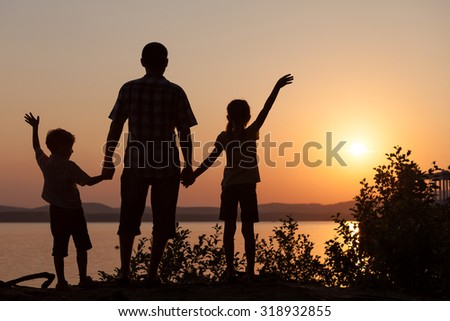 father and children playing on the coast of lake in the mountains of at the sunset time