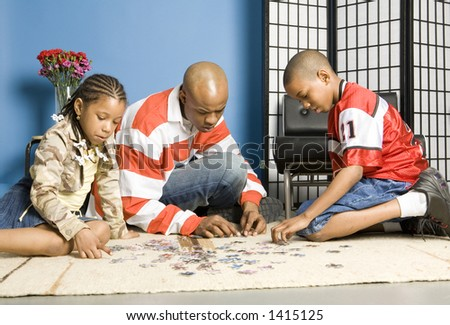 Father and children playing with a jigsaw puzzle - stock photo