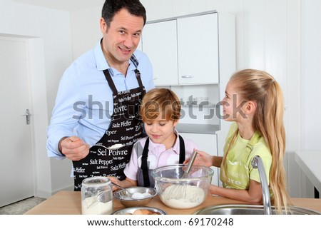 Father and children preparing pancakes - stock photo