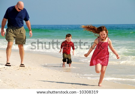Father and children running and playing on pretty beach