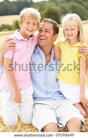Father And Children Sitting On Straw Bales In Harvested Field - stock photo