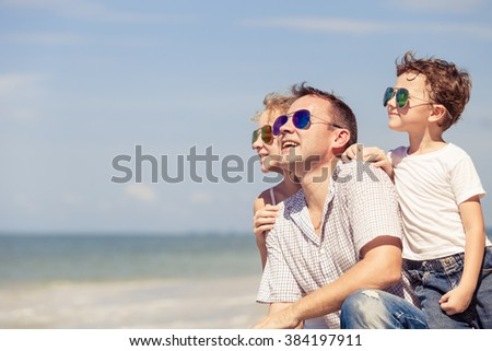 Father and children sitting on the beach at the day time. Concept of happy friendly family. - stock photo