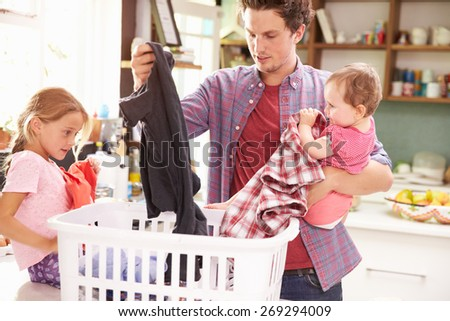 Father And Children Sorting Laundry In Kitchen - stock photo
