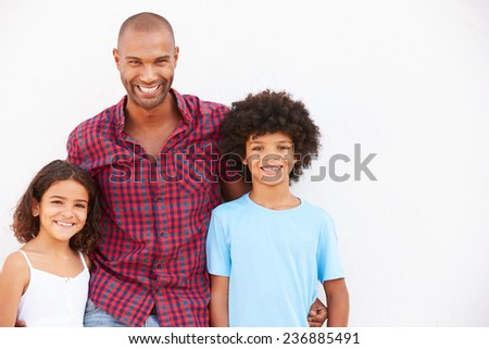 Father And Children Standing Outdoors Against White Wall - stock photo