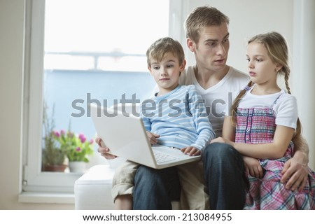 Father and children using laptop while sitting on chair - stock photo