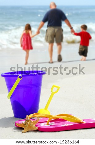 Father and children walking by beach pail, flip flops and starfish on pretty beach - stock photo