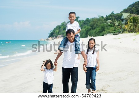 father and children walking on the beach