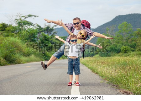 Father and children walking on the road at the day time.  Concept of friendly family. - stock photo