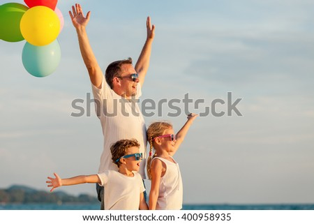 Father and children with balloons playing on the beach at the day time. Concept of friendly family.