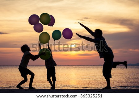 Father and children with balloons playing on the beach at the sunset time. Concept of friendly family. - stock photo