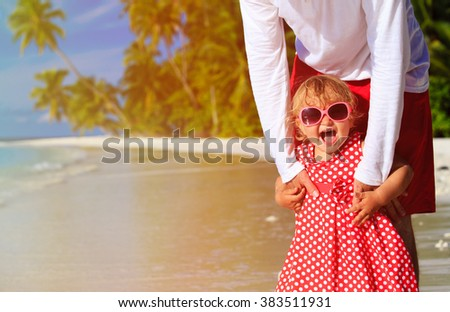 father and cute little daughter at beach - stock photo