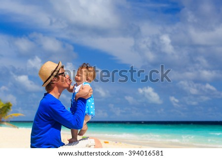 father and cute little daughter play at beach - stock photo
