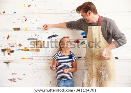 Father And Daughter Against Paint Covered Wall In Art Studio - stock photo