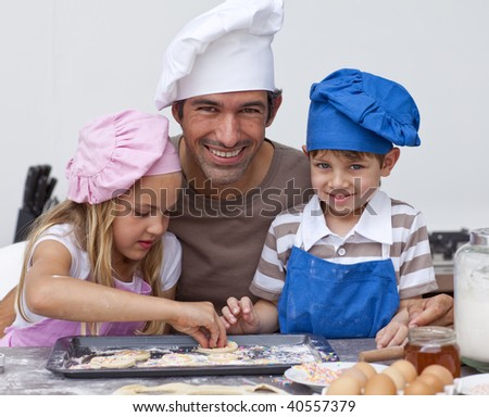 Father and daughter and son baking cookies in the kitchen - stock photo