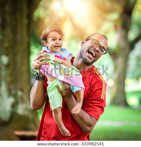 Father and daughter are playing and laughing in the park. African American or Hispanic man with mulatto baby is playing active game. - stock photo