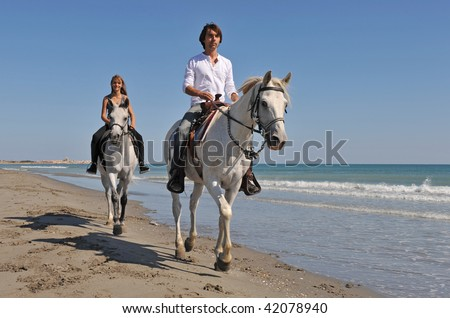 father and daughter are riding with their white horses on the beach - stock photo