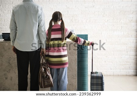 Father and Daughter at Airport Check-In - stock photo