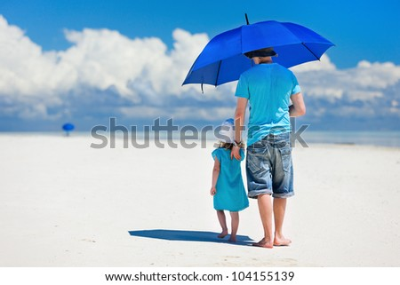 Father and daughter at beach with blue umbrella to hide from the sun - stock photo
