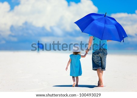 Father and daughter at beach with umbrella to hide from sun - stock photo