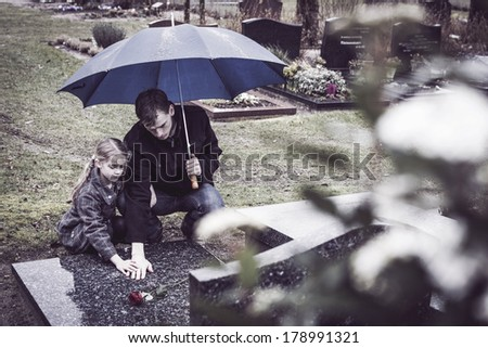 Father and daughter at graveyard visiting grave of mother - stock photo