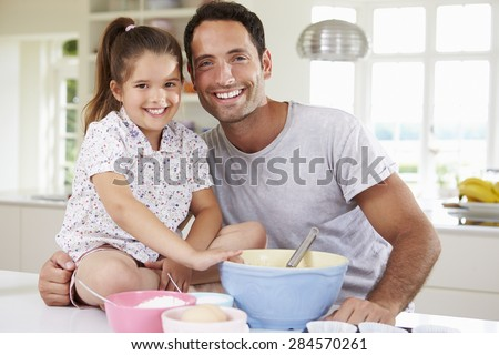 Father And Daughter Baking Cake In Kitchen - stock photo