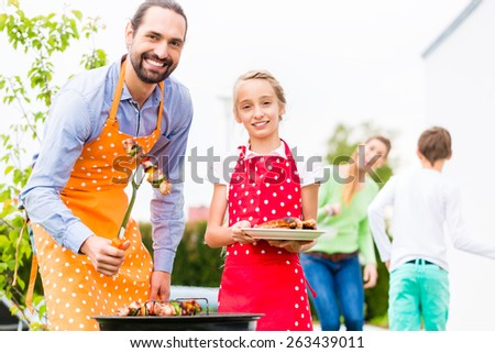 Father and daughter barbecue meat spits and sausages at family garden BBQ  - stock photo