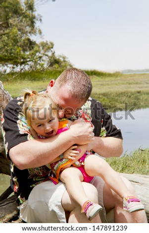 Father and daughter being playful outdoors together. - stock photo