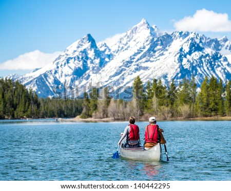 Father and daughter canoeing on Jackson Lake in the Grand Teton National Park. - stock photo