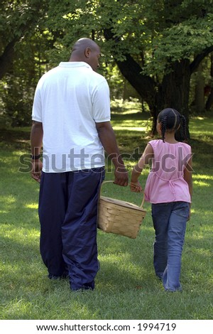 Father and daughter carrying picnic basket together.