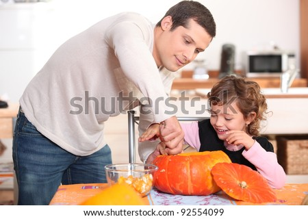 Father and daughter carving pumpkins - stock photo