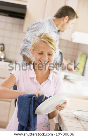 Father And Daughter Cleaning Dishes - stock photo