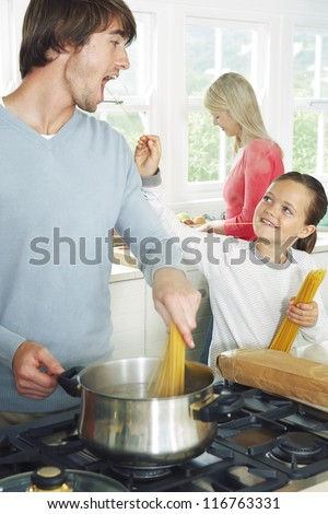 Father and daughter cooking spaghetti in the kitchen with the young girl playfully trying to feed him an uncooked strand - stock photo
