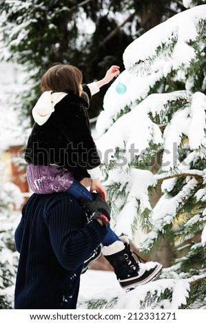 Father and daughter decorating Christmas tree in a winter yard - stock photo