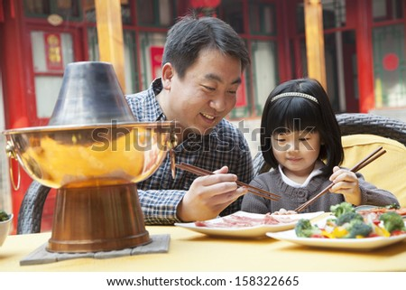 Father and daughter eating Chinese food outside - stock photo