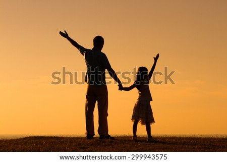 Father and daughter enjoy in sunset together.Father and daughter gretting the sunset - stock photo